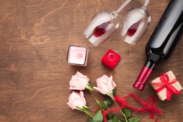 Composición en plano con vino y anillo de compromiso.