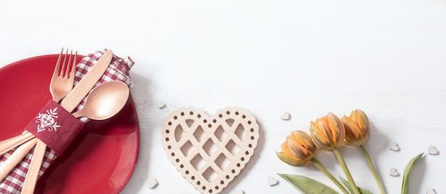 Composición con plato y cubiertos para una cena romántica por san valentín. concepto de citas.