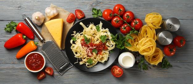 Composición con plato de sabrosas pastas e ingredientes para cocinar en la mesa de madera