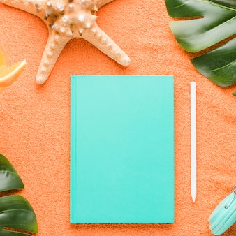 Composición de la playa con el cuaderno en el fondo de color