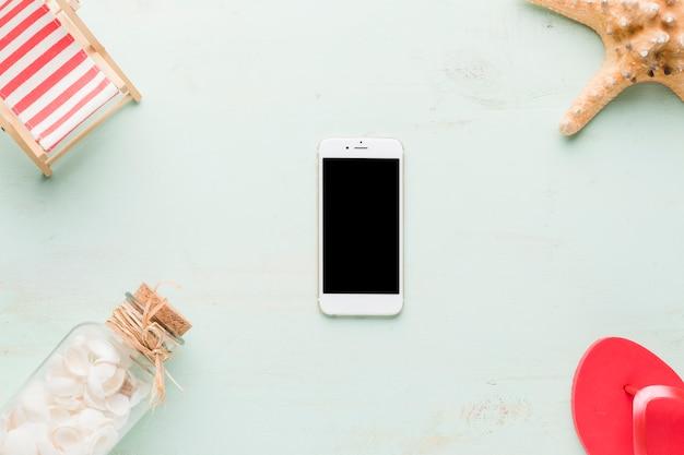 Composición de la playa con el teléfono inteligente sobre fondo claro