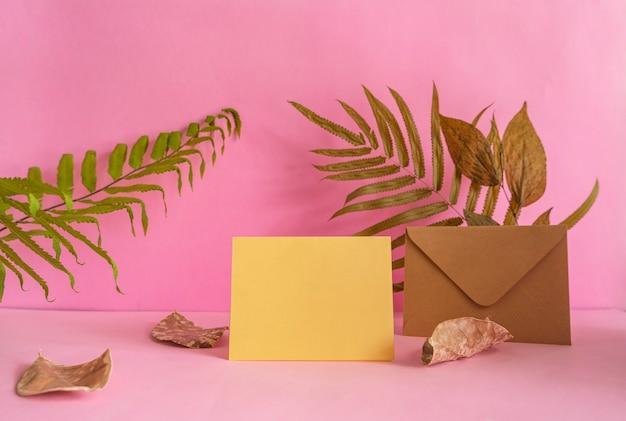La composición presenta productos de verano, madera redonda sobre fondo rosa con decoración de hojas secas.