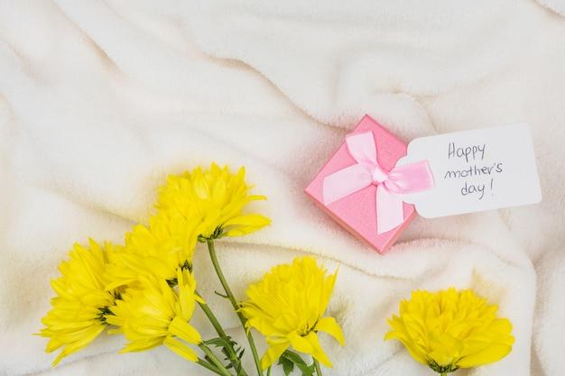 Composición del presente con etiqueta con palabras cerca de flores.