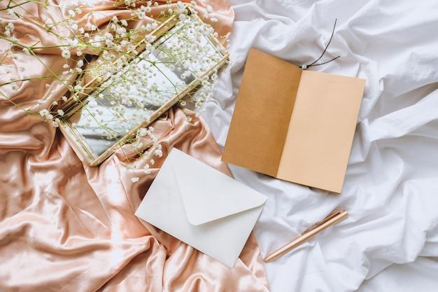 Composición de primavera, flores de gypsophila blancas con cuaderno y bolígrafo sobre la tela de satén dorado