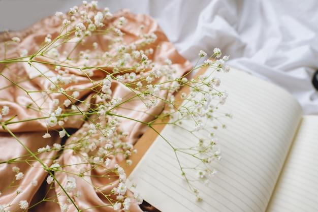 Composición de primavera, flores de gypsophila blancas con cuaderno sobre la tela de satén dorado
