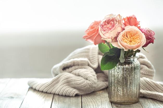 Composición de primavera con flores en un jarrón de vidrio sobre un elemento tejido sobre una mesa de madera.