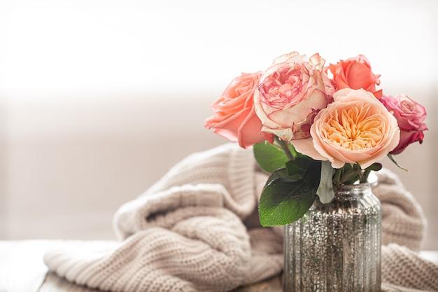 Composición de primavera con flores en un jarrón de vidrio sobre el fondo de un elemento tejido.