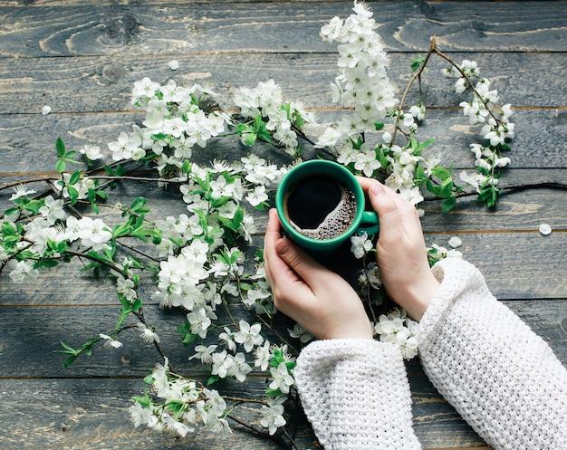 Composición de primavera con reloj vintage y flores en madera oscura