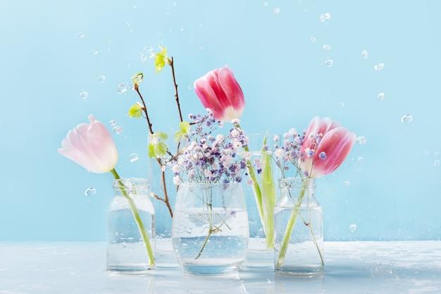 Composición de primavera con rocío de agua de flores frescas de tulipanes rosas y ramas de abedul frescas en vasos