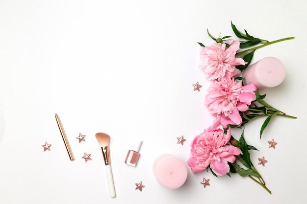 Composición primaveral de flores de peonías, velas rosas, accesorios de mujer.