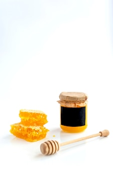 Composición de productos de miel. miel en tarro, panal y cuchara especial. pared blanca