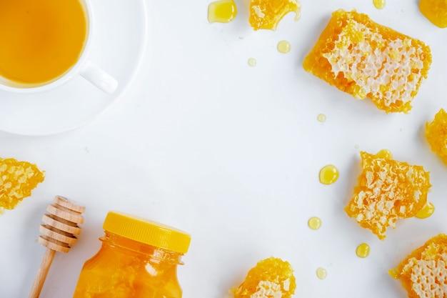Composición de productos de miel. miel en tarro, panal, té y cuchara especial. fondo blanco