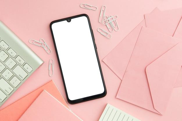Composición de puesto de trabajo rosa plana con teléfono vacío
