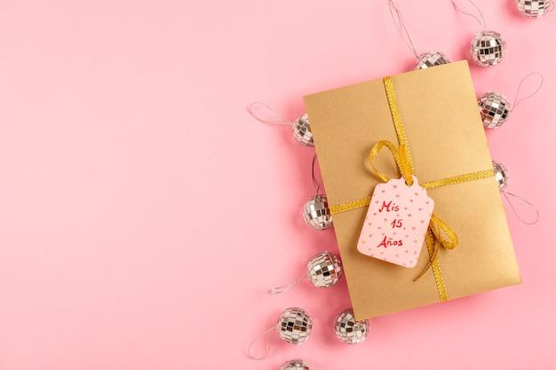 Composición de quinceañera con regalo envuelto con etiqueta