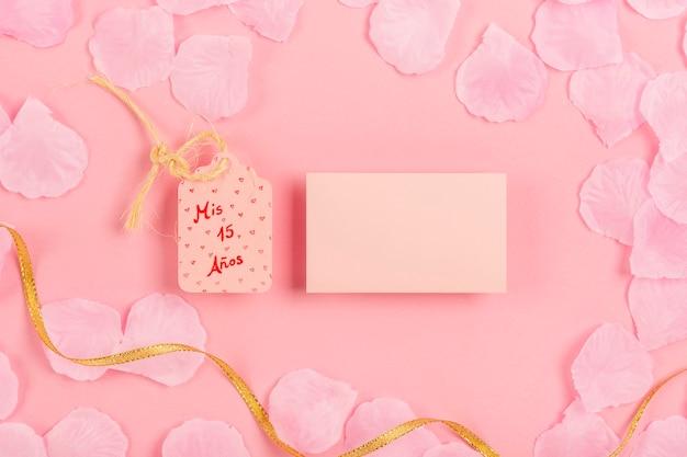 Composición de quinceañera con tarjeta vacía sobre fondo rosa