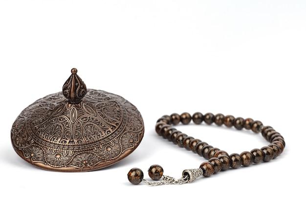 Composición de ramadán con cuentas de oración y plato.