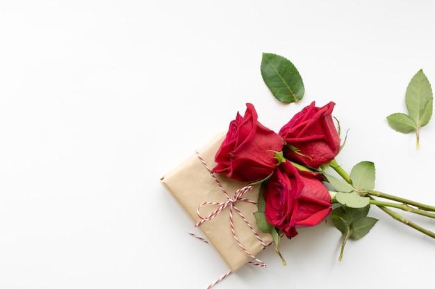 Composición de regalo y ramo de rosas rojas sobre fondo blanco.