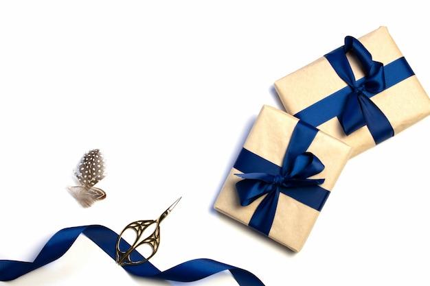 Una composición de regalos empaquetados, papel kraft y cinta azul aislado en un fondo blanco. la vista desde la cima. para maqueta, invitación.