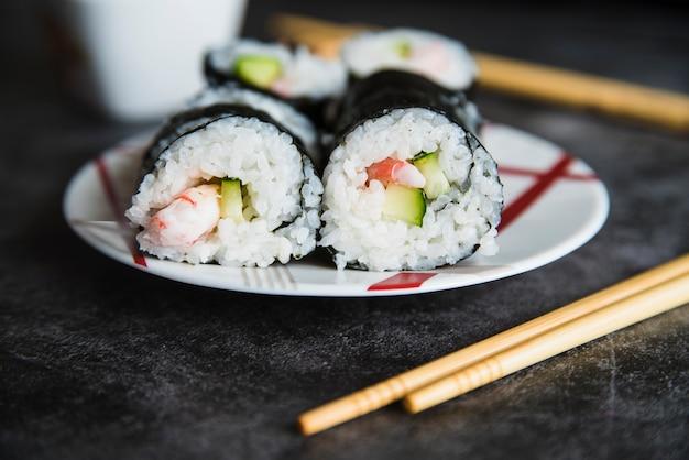 Composición de rollos de sushi en plato y palillos.