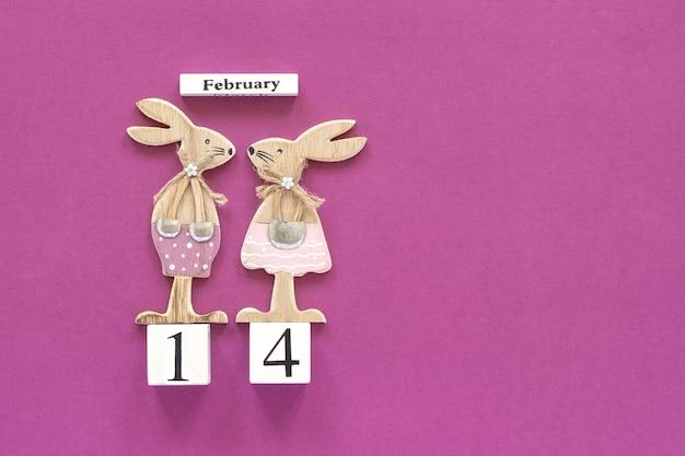 Composición romántica calendario de cubos de madera 14 de febrero y pareja de amantes de madera figurita conejos sobre fondo morado