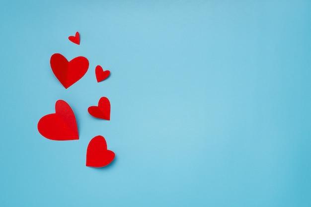 Composición romántica hecha con corazones rojos sobre fondo azul con copyspace para texto