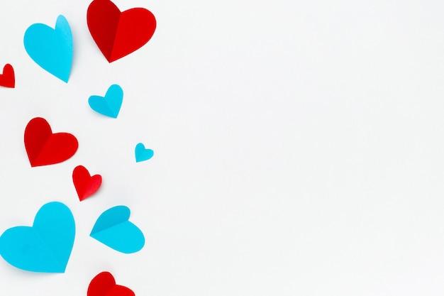 Composición romántica hecha con corazones rojos sobre fondo blanco con copyspace para texto