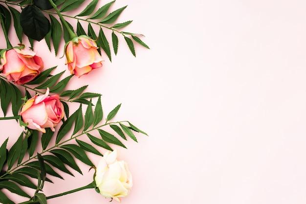 Composición romántica hecha con rosas y hojas de palma.