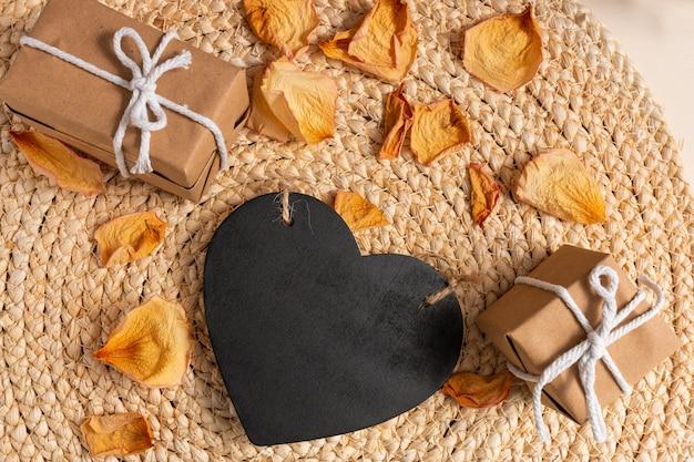 Composición romántica con una pizarra negra en forma de corazón con espacio para texto y cajas de regalo