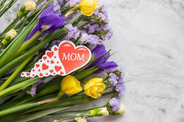 Composición romántica con ramo de narcisos amarillos y flores de lirios púrpuras. feliz día de la madre con espacio de copia.