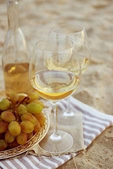 Composición romántica de vino blanco y uva en la playa de arena