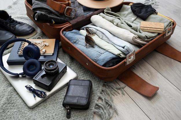 Composición de ropa y accesorios en una maleta.