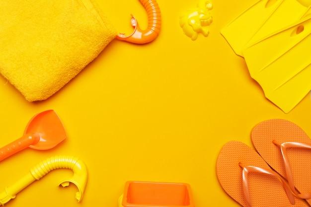 Composición de ropa de playa y accesorios sobre un fondo amarillo.