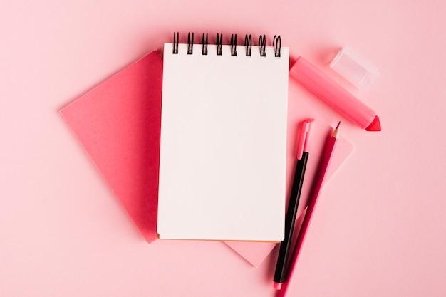 Composición rosa con bloc de notas y material de oficina en superficie de color.
