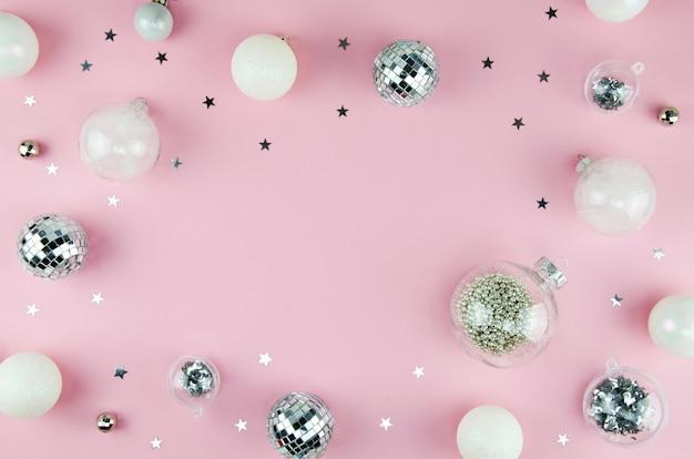 Composición rosa navideña con bolas navideñas y adornos de confeti plateado sobre un fondo rosa