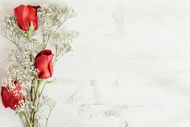 Composición de rosas rojas y flores blancas con espacio de copia