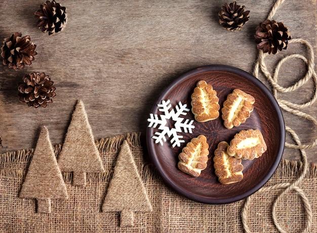 Composición rústica de invierno con galletas de mantequilla en un plato y piñas