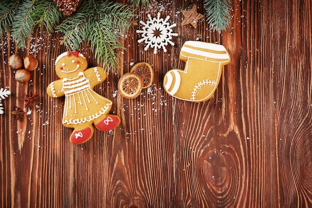 Composición de sabrosas galletas de jengibre y decoración navideña sobre fondo de madera