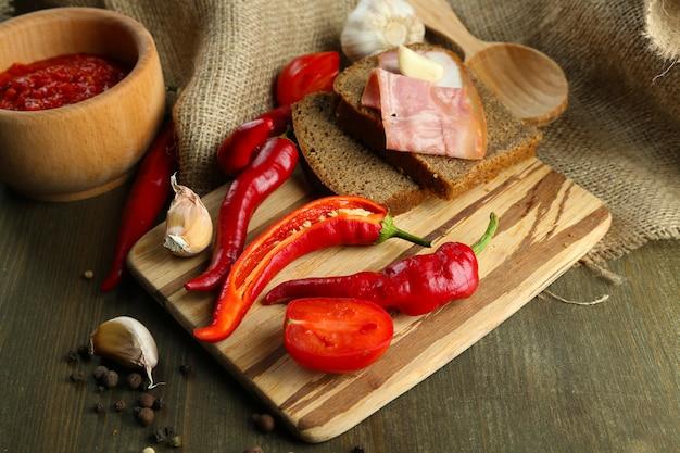 Composición con salsa salsa sobre pan, chiles rojos y ajo, sobre cilicio, sobre madera