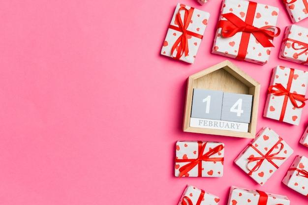 Composición de san valentín de cajas de regalo con corazones rojos y calendario de madera.