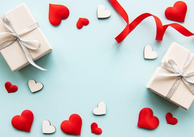 Composición de san valentín con corazones, cajas de regalo y cinta roja.