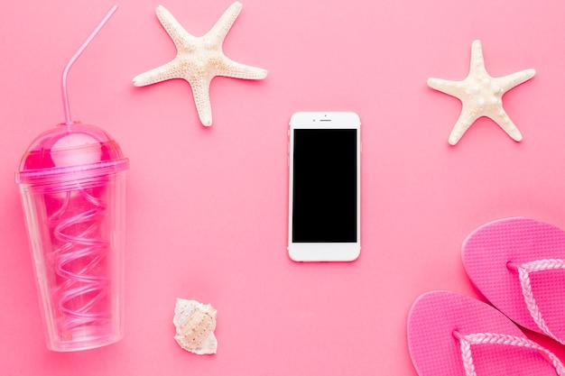 Composición de smartphone coctel estrella de mar y chanclas