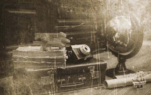 Composición sobre un piso de madera globo vintage con maleta de cuero antiguo con objetos para viajar