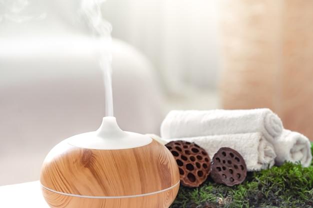 Composición de spa con aroma de moderno difusor de aceite con productos para el cuidado corporal. toallas blancas retorcidas, verdes primaverales y flores. concepto de spa para el cuerpo y la salud.