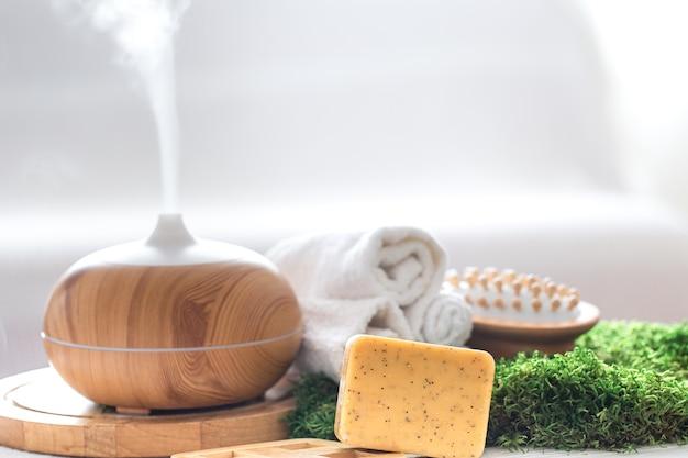 Composición de spa con aroma de moderno difusor de aceite con productos para el cuidado corporal.