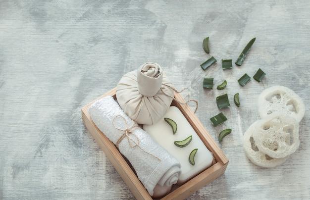 Composición de spa con artículos de cuidado corporal sobre un fondo claro.