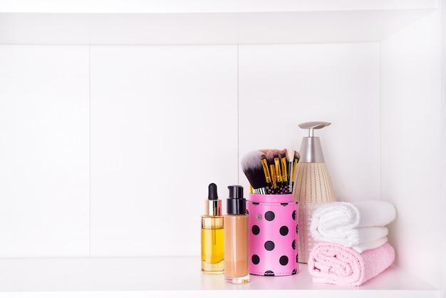Composición con spa cosmética y pincel para cara, aislado en blanco