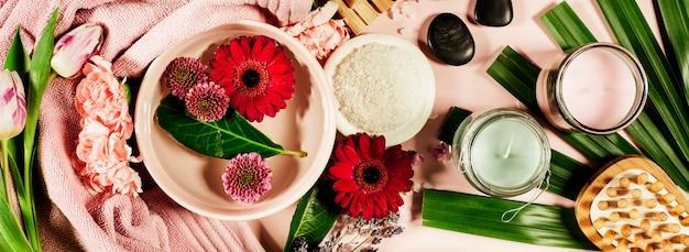 Composición de spa con flores y toalla. lay flat