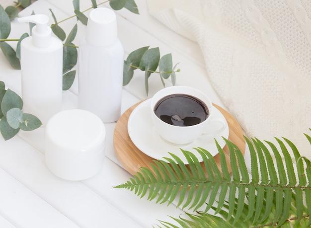 Composición de spa de frasco de crema y botella de champú con taza de café negro.