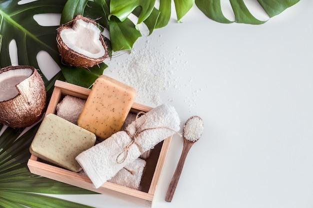Composición de spa con hojas tropicales en mesa blanca