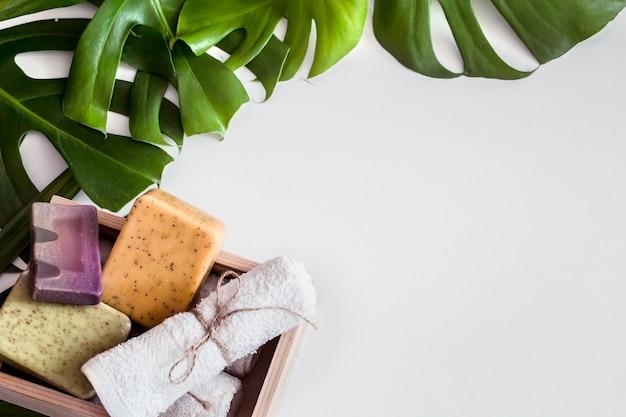 Composición de spa con hojas tropicales sobre un fondo blanco .diferentes jabón orgánico, concepto de cuidado y belleza, vista superior